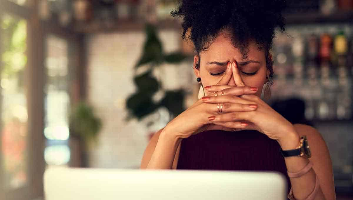 Black woman in front of her laptop suffering from migraine