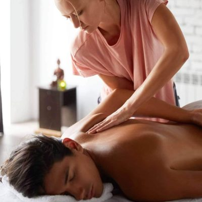 Massage therapist giving massage to young man