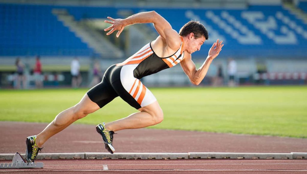 Man athlete running in field at fast pace