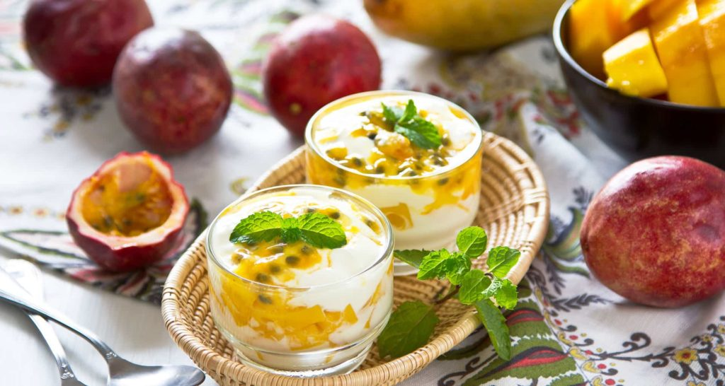 Passion fruit mango-mint lassi on glass with the fruits