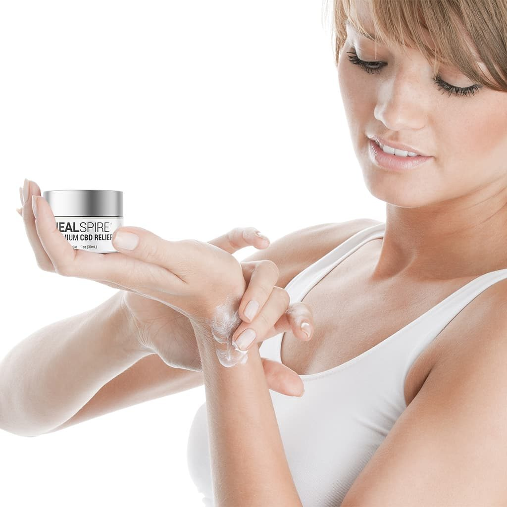 Woman applying healspire CBD relief rub on her wrist